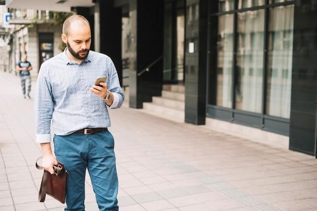 Uomo elegante che cammina per strada con smartphone