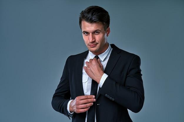 Elegant man wearing tuxedo on gray room