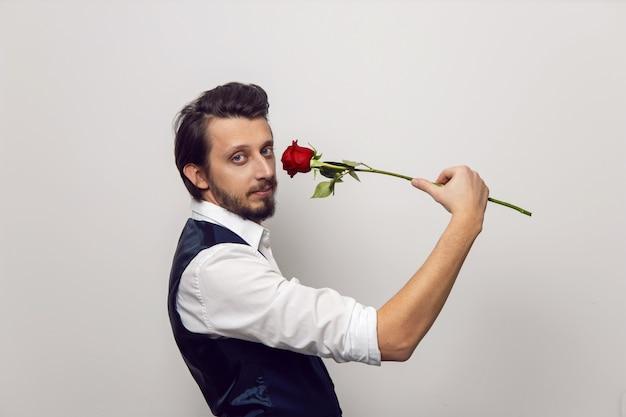 白いシャツと白い壁のベストでバレンタインデーにひげと眼鏡をかけたエレガントな男は赤いバラで立っています