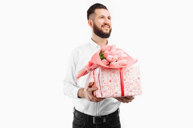 Элегантный мужчина с бородой держит букет тюльпанов и подарочную коробку, подарок на день святого валентина