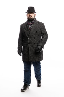 Elegant man with a beard in a coat and hat. full-length stands on a white wall. vertical.