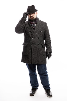 Elegant man with a beard in a coat and hat. he stands in full growth on a white wall and holds on to his hat. vertical.
