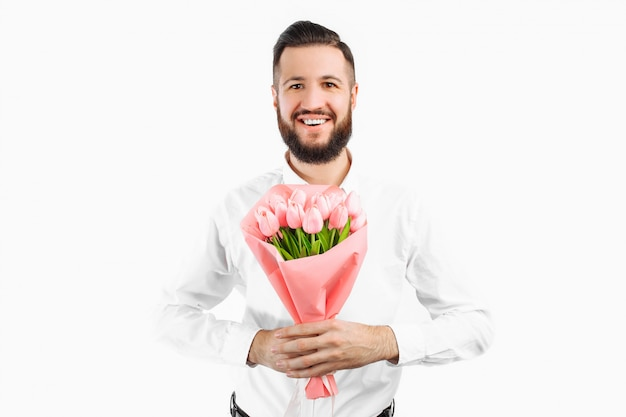 Elegant man with a beard holding a bouquet of tulips, a gift for valentine's day