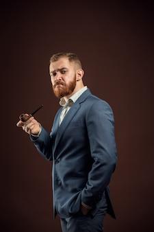Elegant man with beard holding smoking pipe