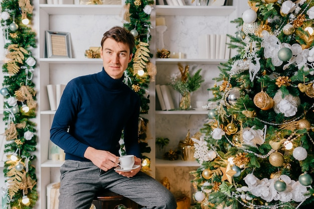 Elegant man with positive emotional face posing for camera with cup of coffee in cozy room with cristmas tree and new year decorations