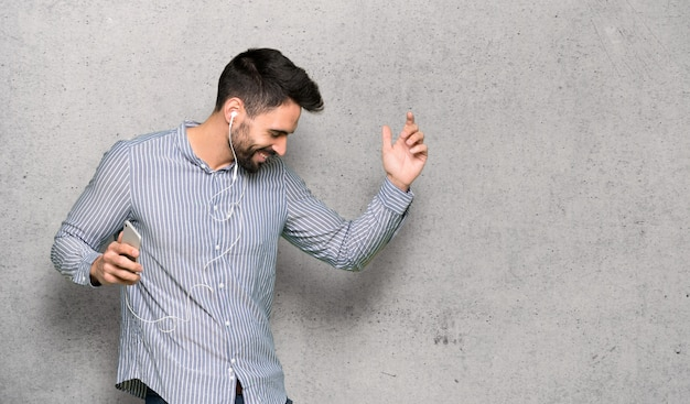 Elegant man with shirt listening music with the phone over textured wall