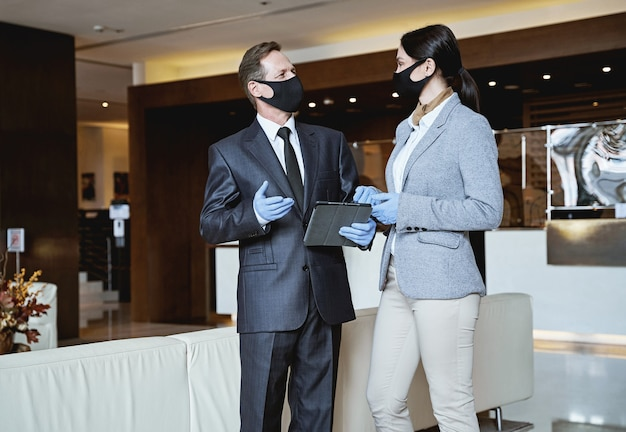 Elegant man and woman in medical masks and rubber gloves looking at each other while communication in a hotel lobby