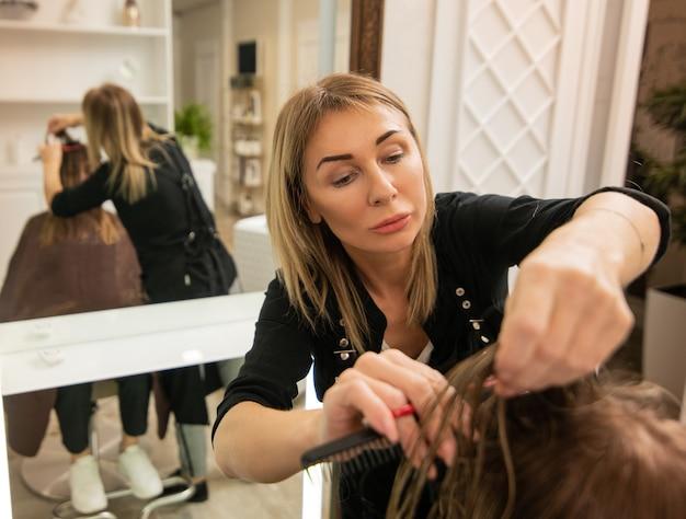 美容院でクライアントの髪を切るエレガントな成熟した美容師の女性。美容コンセプト