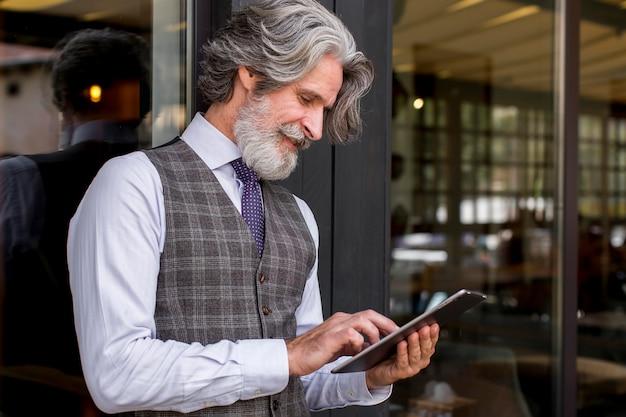 Elegante tablet maschio maturo di navigazione