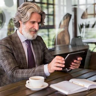 オフィスでタブレットを保持しているエレガントな成熟した男性