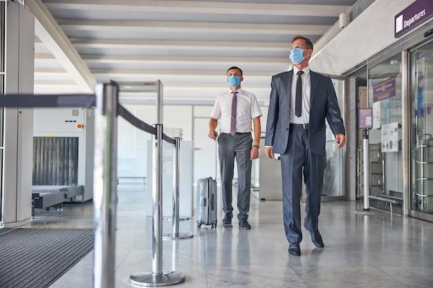 그의 조수가 짐을 나르고 마스크를 쓰고 있는 동안 우아한 성숙한 남성이 여행을 갑니다