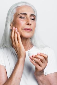 Elegant mature woman applying moisturizer