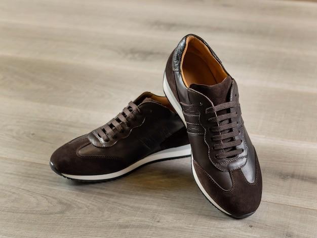 밝은 나무 배경 측면의 스포티한 스타일의 우아한 남성용 신발