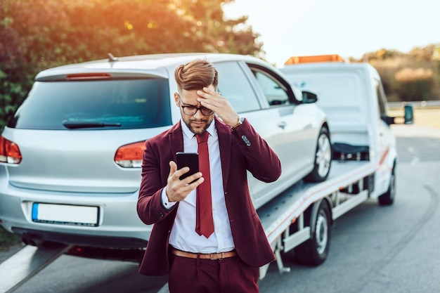 Элегантный деловой человек среднего возраста, вызывающий службу буксировки за помощью на дороге. концепция помощи на дороге.