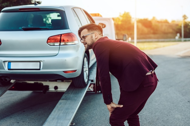 Элегантный деловой человек среднего возраста, использующий услуги буксировки для помощи в автокатастрофе на дороге. концепция помощи на дороге.