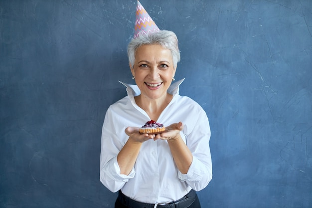 Элегантный мужчина средних лет в белой рубашке празднует годовщину, позирует изолированно со свежеиспеченным пирогом, с радостным выражением лица
