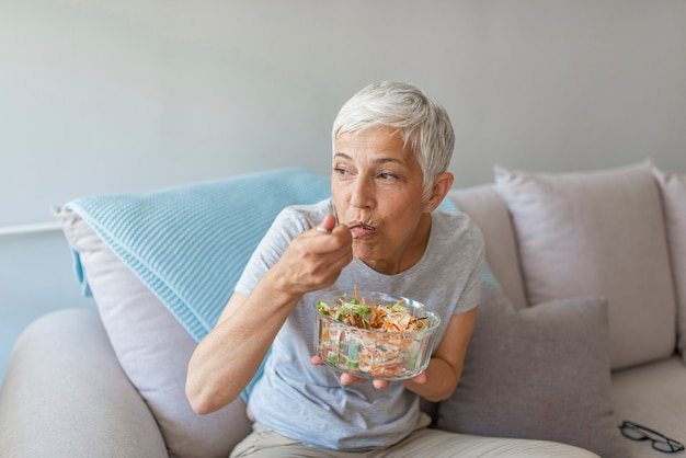 Elegant middle aged woman sitting on bed and eating salad. happy old lady eating fresh green salad, smiling.