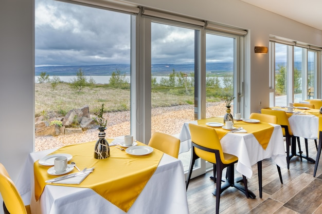 Elegant and minimalist restaurant in a scandinavian hotel with fantastic views of the countryside and mountains