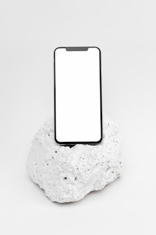 Elegant minimalistic white stone piece with stationery and smartphone