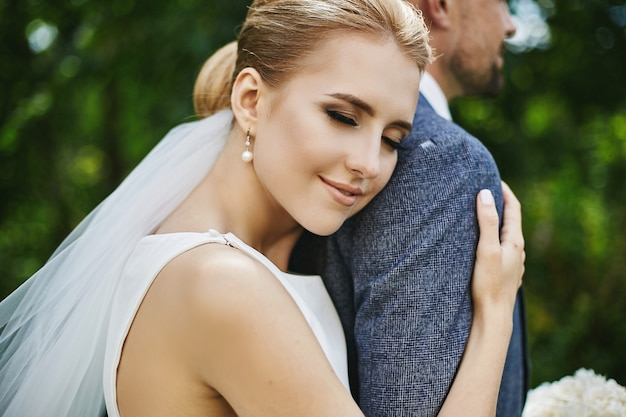 Elegant model girl with wedding coiffure in trendy white dress leaning on handsome groom and posing outdoors