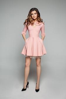 Элегантная модель в розовом платье и черных каблуках.