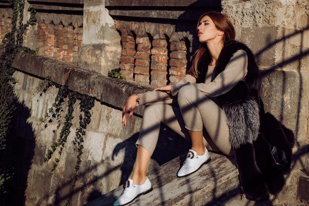 풍성한 의상과 푹신한 모피 코트의 우아한 모델. 세련된 모습과 긴 검은 머리를 가진 아름다운 소녀가 푹신한 진짜 모피 코트를 입고 도시 거리를 걷고 있습니다. 럭셔리 패션 스타일 개념입니다.