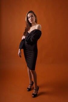 오렌지 배경에 포즈를 취하는 검은 드레스와 하이힐 신발을 신고 우아한 모델