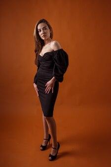 검은 드레스와 하이힐 신발을 입고 포즈를 취하는 우아한 모델