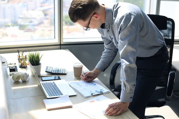 사무실에서 일하는 동안 데이터를 분석하는 우아한 현대 사업가입니다.