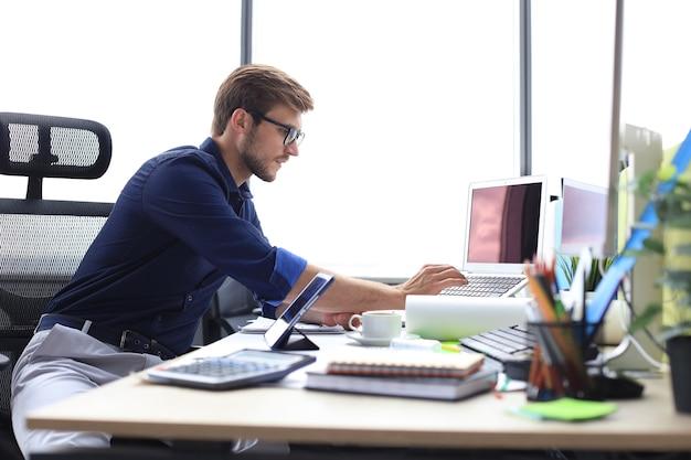 オフィスで働いている間データを分析するエレガントな現代のビジネスマン。