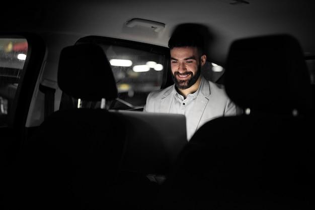 우아한 현대 사업가는 그의 차 뒷좌석에 노력하고 있습니다.