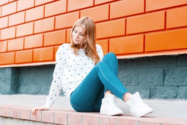 우아한 현대 젊은 쾌활한 여자 운동화 유행 청바지에 흰색 스웨터에 금발 거리에 현대 오렌지 건물 근처 바닥에 앉아