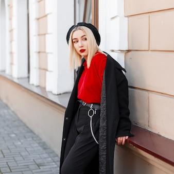 秋の日のヴィンテージの建物の近くのスタイリッシュなズボンでファッショナブルなロングコートと赤いシャツのベレー帽のエレガントでモダンな若い女性