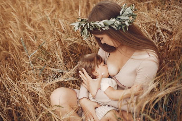 Elegant mother with cute little daughter in a field