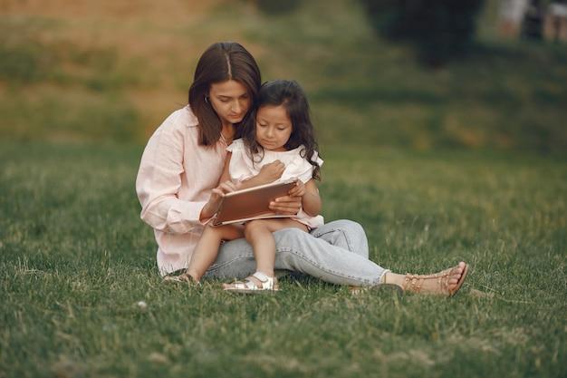 여름 공원에서 딸과 함께 우아한 어머니