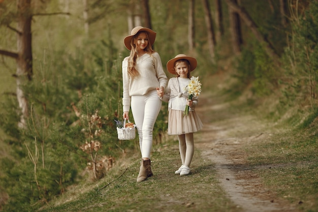 Elegant mother with daughter in a summer forest