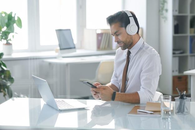 Элегантный офисный работник в наушниках сидит за столом и ищет саундтрек в смартфоне