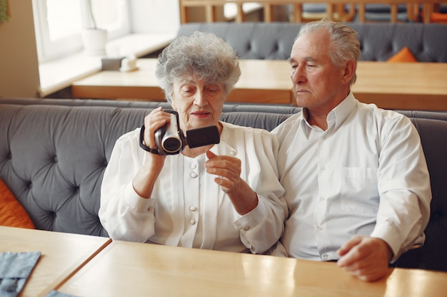 Elegant old couple in a cafe using a camera