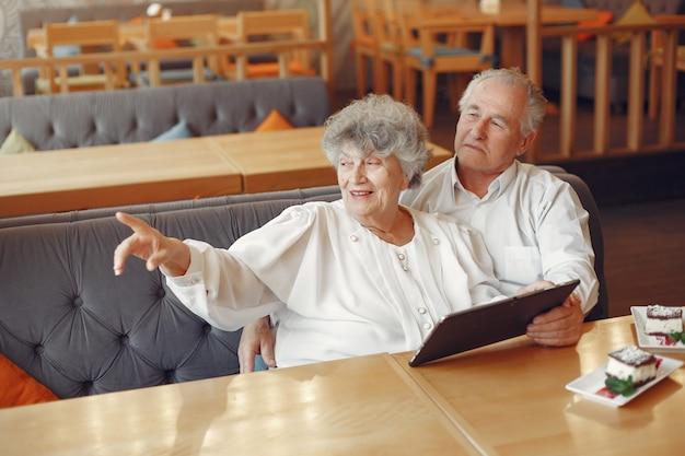 Элегантная старая пара в кафе с помощью планшета