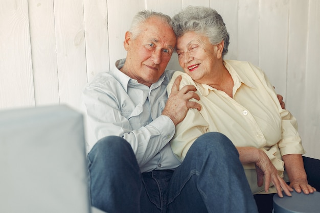 Elegant old couple sitting at home on a foor