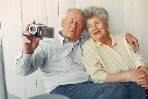 Elegant old couple sitting at home and using a camera