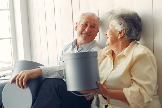 Elegant old couple sitting at home with christmas gifts