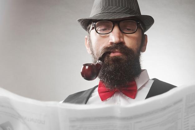 Элегантный старомодный бородатый хипстер среднего возраста с курительной трубкой