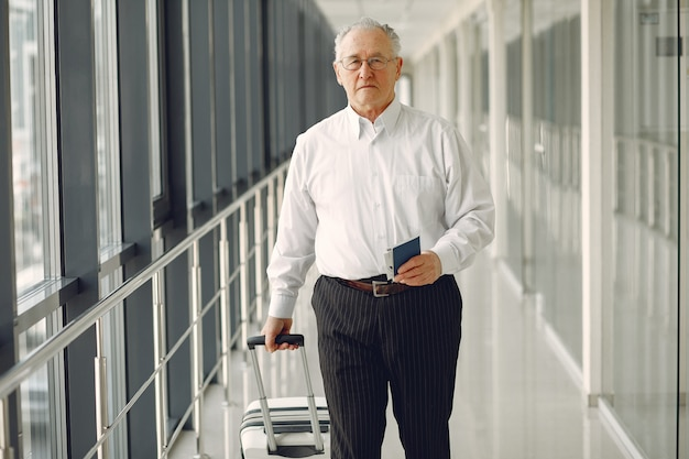 Elegant old man at the airport with a suitcase