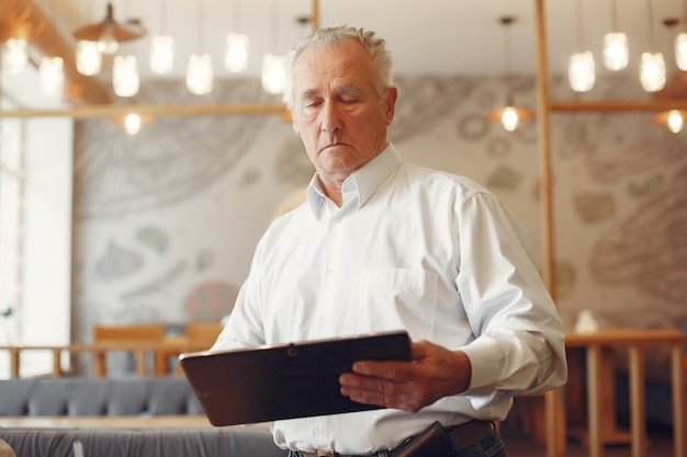 Elegant old man in a cafe using a laptop