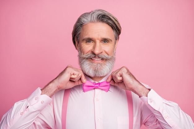 Элегантный старик, фиксирующий бабочку на розовом фоне