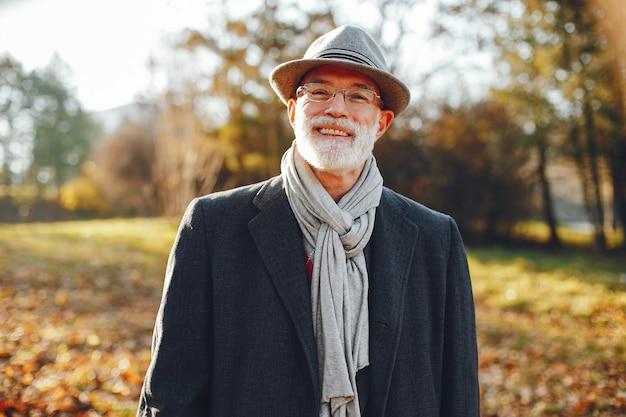 Элегантный старик в солнечном осеннем парке