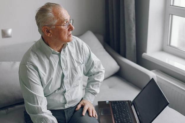 エレガントな老人が家で座っているとラップトップを使用して