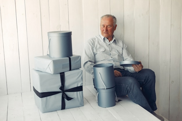 크리스마스 선물 집에 앉아 우아한 노인