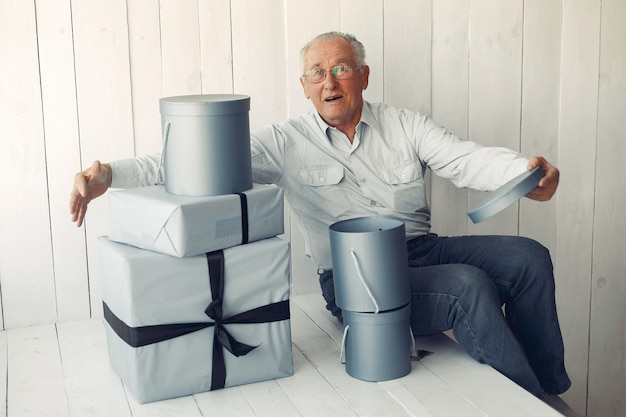 Elegant old man sitting at home with christmas presents